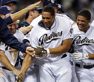 Kyle Blanks (center) is mobbed by his teammates after hitting his walk-off, three-run blast.  (AP)