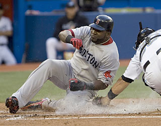 David Ortiz, who slides safely past catcher Rod Barajas, scores three times and provides a HR and three RBI.  (AP)