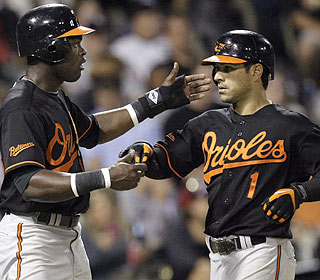Felix Pie is the first to greet Brian Roberts after the latter's go-ahead homer in the eighth. (AP)