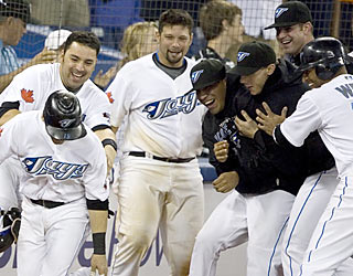 Marco Scutaro (left) creates a Blue Jay frenzy after he scores the winning run in the ninth inning.  (AP)