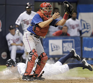 Brendan Harris slides safely past Ivan Rodriguez and scores the final run in the Twins' big eighth inning.  (AP)