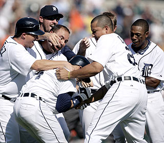Placido Polanco gets mobbed after hitting the winner for Detroit, which ups its division lead to five games. (AP)