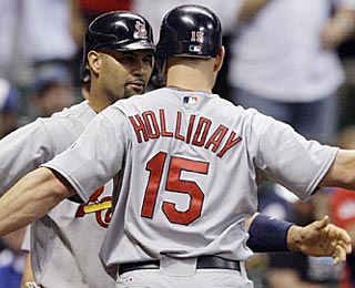 Matt Holliday gets a big welcome from Albert Pujols after his game-changing home run in the ninth.  (AP)