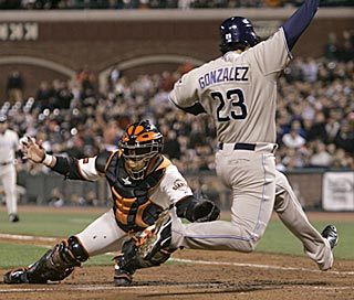 San Diego's Adrian Gonzalez slides past Bengie Molina with the winning run in the eighth inning.  (AP)