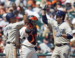 Everth Cabrera waits at the plate to congratulate Adrian Gonzalez, who clubs a two-run homer in the third.  (AP)