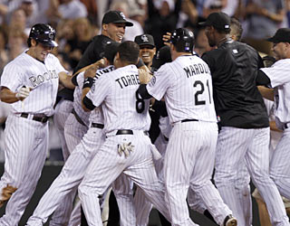 Somewhere in the middle of the Rockies' mob is hero Seth Smith, who helps Colorado win its sixth straight.  (AP)