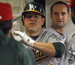 Jack Cust hits the welcome wagon in the Oakland dugout after hitting his 22nd homer of the year. (AP)