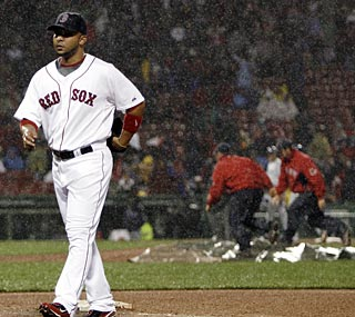 Alex Gonzalez walks off the field in a downpour, but the Red Sox are able to take a needed win.  (AP)