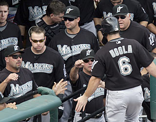 The Marlins wait in the dugout to greet the player who scores in the eighth ... and his name is Dan Uggla. (AP)