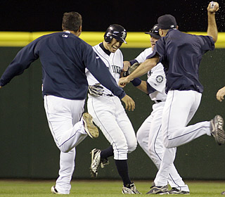 Ichiro (second from left) sets off a Seattle celebration with his game-winning single in the 14th.  (AP)