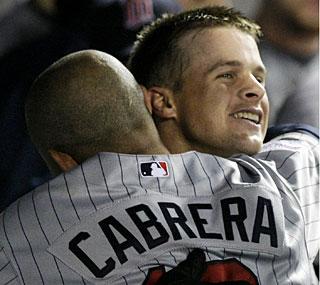 Matt Tolbert receives a hug from Orlando Cabrera after his home run in the sixth inning.  (AP)