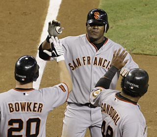 Juan Uribe is met by the Giants welcoming committee after his sixth-inning home run.  (AP)