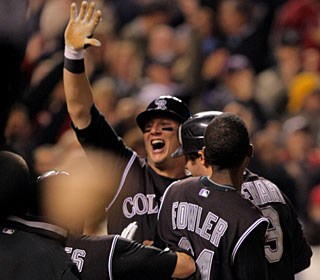 The celebration is on for the Rockies after Troy Tulowitzki scores the winning run on a sac fly. (Getty Images)