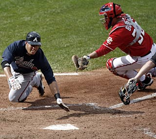 The Braves' Yunel Escobar avoids the tag and slides home as Atlanta continues to win.  (AP)