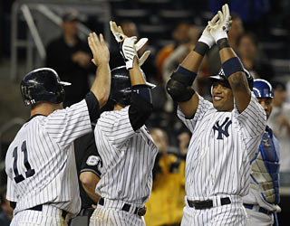 Robinson Cano (right) greets a couple of Yankees moments after hitting his second career grand slam.  (AP)