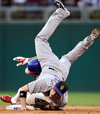 Second baseman Clint Barmes flips over Pedro Feliz, turning a double play in the sixth inning.  (Getty Images)