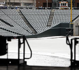 Coors Field is desolate and covered in snow on Saturday, but the weather should clear up for Sunday.  (AP)