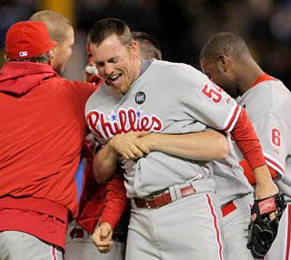 The Phillies embrace closer Brad Lidge, who closes out the Rockies' chances in Game 4 with a one-out save.
