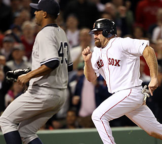 Kevin Youkilis scampers home on a passed ball in the seventh for the winning run.  (Getty Images)