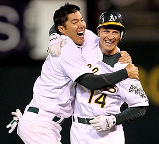 Oakland catcher Kurt Suzuki is the first to congratulate Mark Ellis on his game-winning hit.  (Getty Images)
