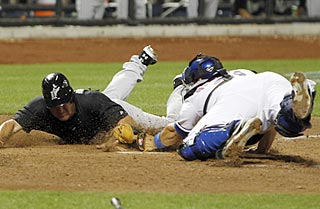 Wes Helms touches home plate an instant before Rod Barajas tags him in the top of the 10th.  (US Presswire)