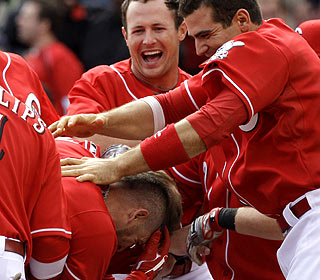 Jonny Gomes gets mobbed by teammates after sending a 2-2 pitch over the fence in the bottom of the ninth. (AP)