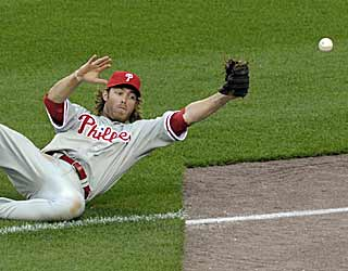 Ryan Zimmerman's blooper falls just outside of the reach of the sliding Jayson Werth. (AP)