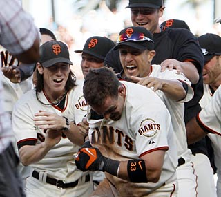 The Giants mob Aaron Rowand after he knocks in the winning run with two outs in the 13th inning.  (AP)