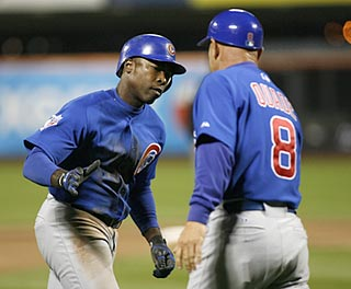 Cubs third-base coach Mike Quade greets Alfonso Soriano after his seventh-inning home run.  (US Presswire)