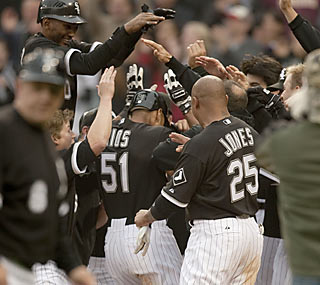A band of happy White Sox players congratulate Alex Rios, who blasts a game-winning HR in the ninth.  (AP)