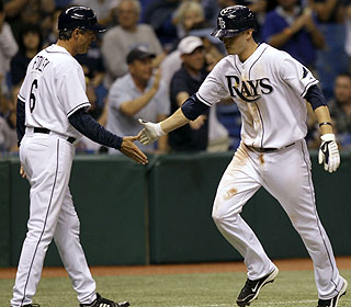 Reid Brignac (right), who gets a handshake from his third-base coach, helps Tampa Bay move to 15-5. (AP)