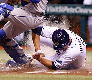 The Rays' Pat Burrell slides in under the Royals' Jason Kendall for a hard-earned run. (US Presswire)