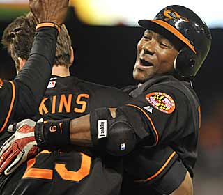 Miguel Tejada is mobbed by teammates after his game-winning single in the 10th. (AP)