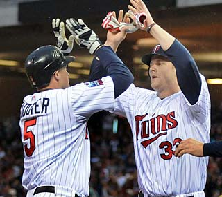 The Twins' Michael Cuddyer (left) is greeted at home plate after drilling a three-run homer.  (AP)