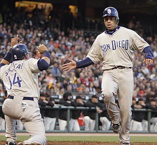 Padres teammates Oscar Salazar (14) and Jerry Hairston Jr. score on David Eckstein's hit in the second.  (AP)
