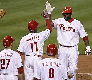 It's high-fives all around for slugger Ryan Howard after hitting a grand slam in the eighth inning. (AP)