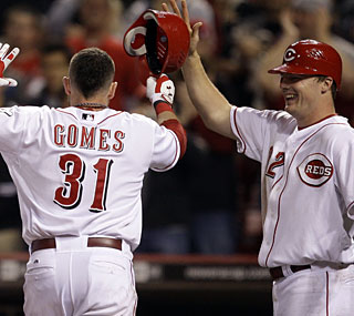 The Reds can only smile as Jonny Gomes crosses home plate following his three-run homer in the seventh.  (AP)