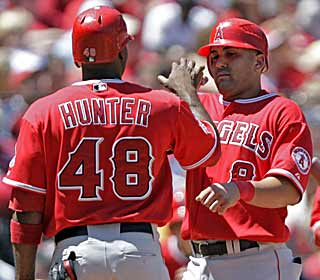 Kendry Morales (right) finishes with three hits, leading a hit parade for the Angels, who tally 13 in total.  (AP)