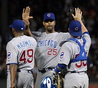 Derrek Lee (middle) and the Cubs win in Arlington to end Texas' winning streak.  (AP)