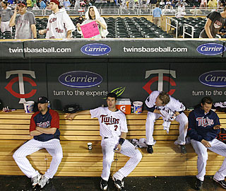 Twins players wait in the dugout while it rains before the game is eventually suspended. (AP)