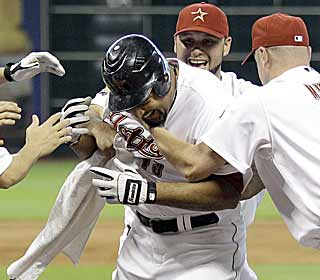 Carlos Lee is swarmed by teammates after his two-run blast in the ninth wins it for the Astros. (AP)