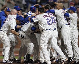 Beneath this mob stands Ike Davis, who plays the role of hero in the Mets' extra-inning win.  (Getty Images)