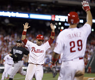 Raul Ibanez watches on as Placido Polanco and Chase Utley (left) score to give Philly the lead in the eighth.  (AP)