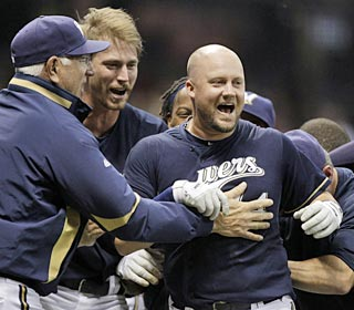 The Brewers swarm around a jubliant Casey McGehee, who delivers the game-winning, two-run single.  (AP)