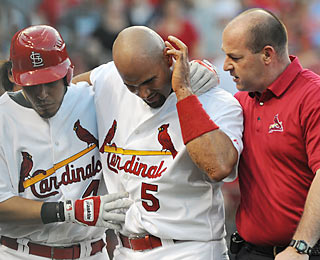 Albert Pujols, who gets his bell rung from a ball to the head, is perfect at the plate (three hits, two walks). (AP)
