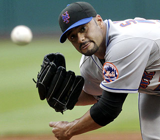 Johan Santana gives up four runs and seven hits over seven innings in his first win in four starts. (AP)