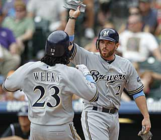 Rickie Weeks and Joe Inglett come in to score in the ninth as the Brewers pile runs on the Rockies. (AP)