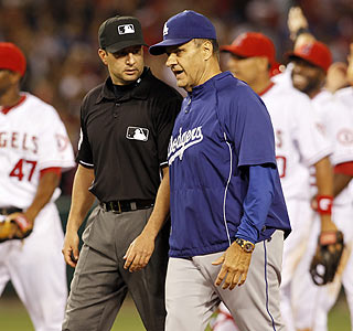 Joe Torre gets an explanation from second-base ump Jim Reynolds as the Angels celebrate the win.  (AP)
