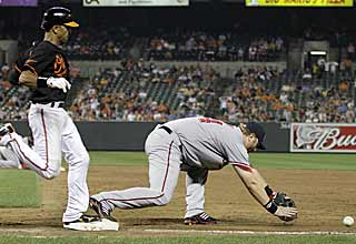 Adam Dunn can't handle the throw at first which leads to the Orioles scoring the winning run. (AP)