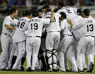 The Marlins swarm the field moments after Dan Uggla singles in the winning run with two outs in the ninth.  (AP)